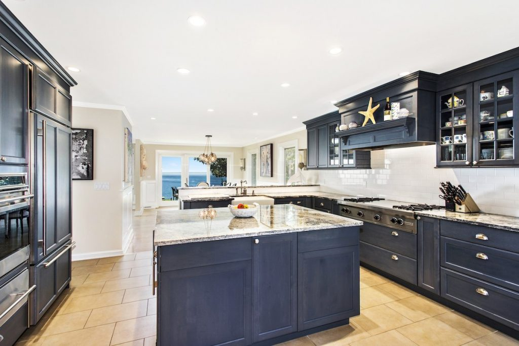 Exquisite kitchen with navy cabinets and granite countertops.